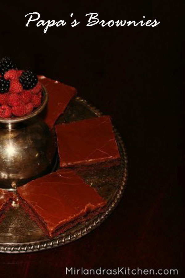 A antique silver plate is loaded up with slices of Texas sheet cake. In the center a silver goblet holds raspberries and blackberries.