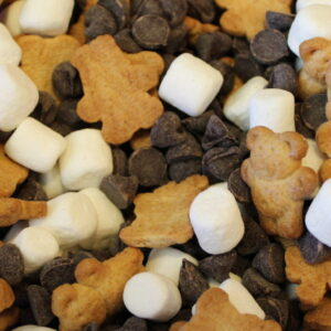 This is a close up image of smores snacke mix. You can see teddy grahams, mini marshmallows and chocolate chips all mixed together waiting to be munched on.