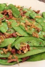 tender green snow peas are sauteed with bacon and topped with crispy french fried onions on a white plate.