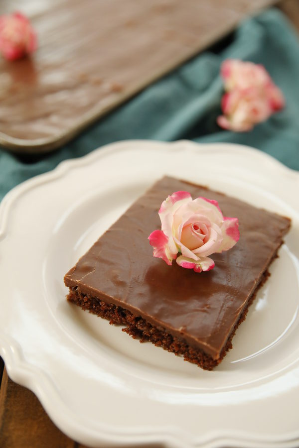 A big slice of Texas sheet cake sits on a white plate. The pan of cake is in the background and a few pink roses are scattered around.