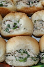 Fresh yeasty rolls are stuffed with classic chicken salad. You can see shredded chicken, sauce, celery, and other green herbs in the salad.