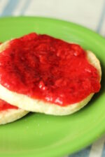 strawberry freezer jam is slathered in a thick layer on toasted English muffins. Two muffins with jam rest on a bright green plate.