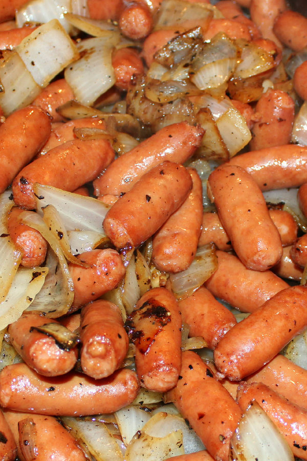 A close up shows a bit platter of litl smokies sausages cooked up with large chunks of caramelized onions for breakfast.