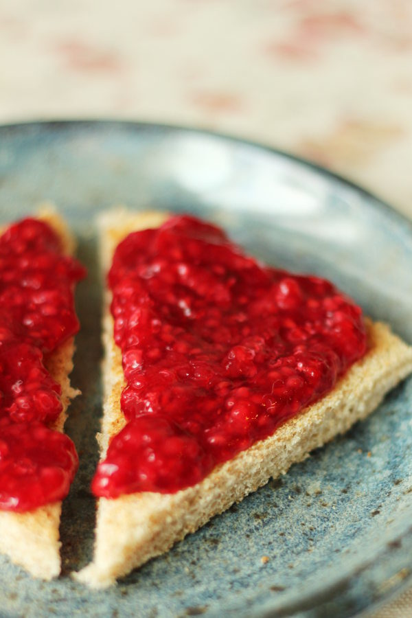 A slice of toast is cut into two triangles and slathered with no cook raspberry jam.  The toast is on a blue stoneware plate.