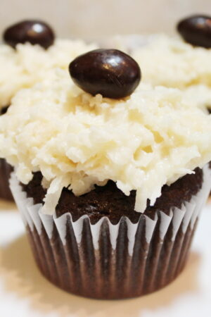 Three almond joy cupcakes sit on a white plate. You can see the chocolate cupcake, the coconut frosting and a chocolate coconut almond on top.
