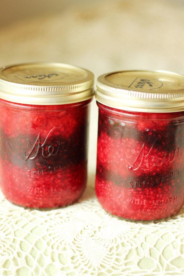 Two jars of no cook berry jam.  The jam has been layered into the jar in stripes so you can see a layer of raspberry, layer of blackberry, and layer of strawberry.