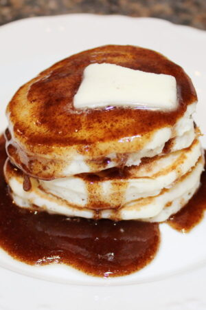 A stack of pancakes is covered with sticky bun pancake syrup with a pat of butter on the top.