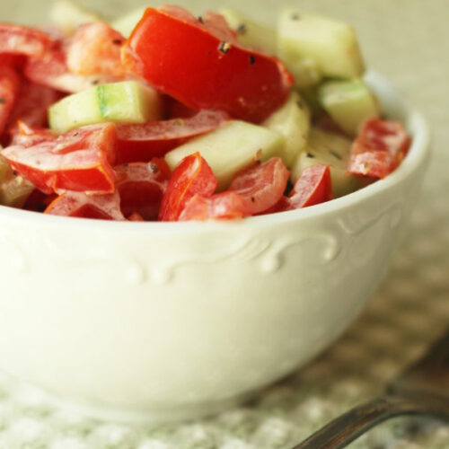A white bowl is full of creamy tomato and cucumber salad with a mayonnaise dressing. The bowl is sitting on a green and white checked table cloth next to an antique silver fork.