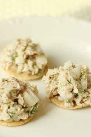 Three rice crackers are loaded up with mounds of healthy tuna salad. You can see fresh dill and small pieces of onion.