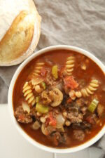 A hearty bowl of beef minestrone soup sits on a white table. There is a gray cloth on the rustic farmhouse table and a loaf of artisan bread next to the bowl. The soup is full of mushrooms, carrots, celery, and pasta.