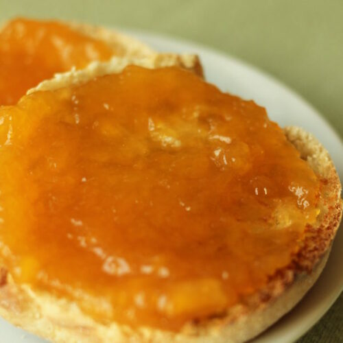 A small white plate holds a toasted English muffing smothered with fresh peach jam. The jam is a rich amber color.
