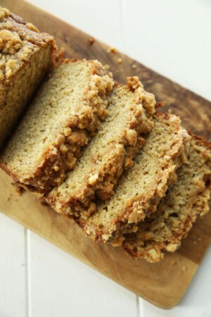 Slices of banana bread sit on a wooden cutting board ready to be eaten.