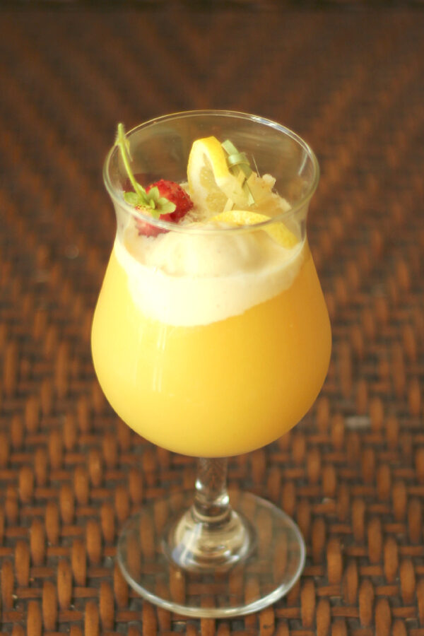 A tropical cocktail glass is full of a pineapple vodka cocktail based on the Dole Whip flavor. There is a scoop of ice cream, a strawberry and some lemon slices as garnish.
