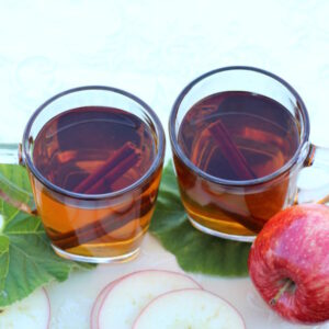 Two cups of mulled apple cider are ready to drink. Apple slices are nearby on the table.