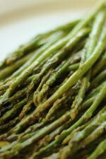 Asparagus that has been roasted in miso paste is lying on a white platter ready to serve for dinner.