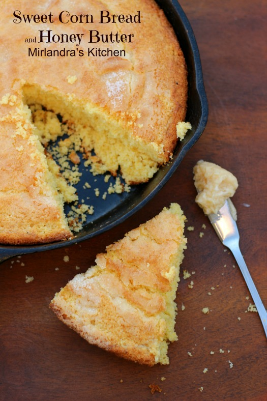 Golden corn bread with a sugar crust is baked in a cast iron skillet.  There is a wedge sitting on the table next to a dollop of butter ready to spread.