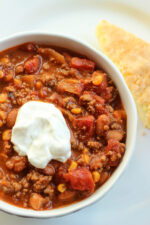 A big white bowl is full of meaty beef and bean chili. You can see chunks of tomatoes and pieces of corn. There is a dollop of sour cream on top.