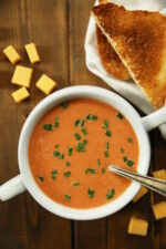 A white soup bowl with two handles is full of homemade tomato soup. The soup is a rich orange and garnished with some chopped chives. An old fashioned silver spoon is in the soup and chunks of cheddar cheese sit nearby as does a some toasted bread.