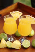 Two glasses sit on a tray surrounded by chunks of pineapples and cut limes. The glasses each have a strong mai tai in them and a wedge of pineapple on the rim.