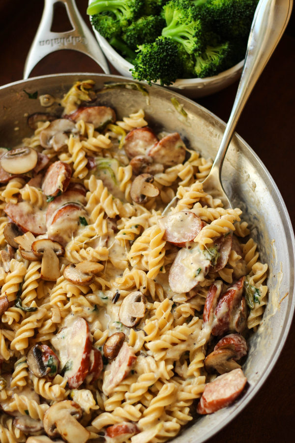 A large skillet is full of spiral noodles, Alfredo sauce, and slices of sausage. There is a bowl of steamed broccoli in the background.