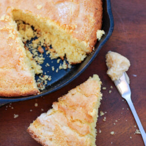 A cast iron pan is full of corn bread. The top is sparkling from a dusting of sugar and one wedge has been cut out and set on the table next to a knife full of honey butter.