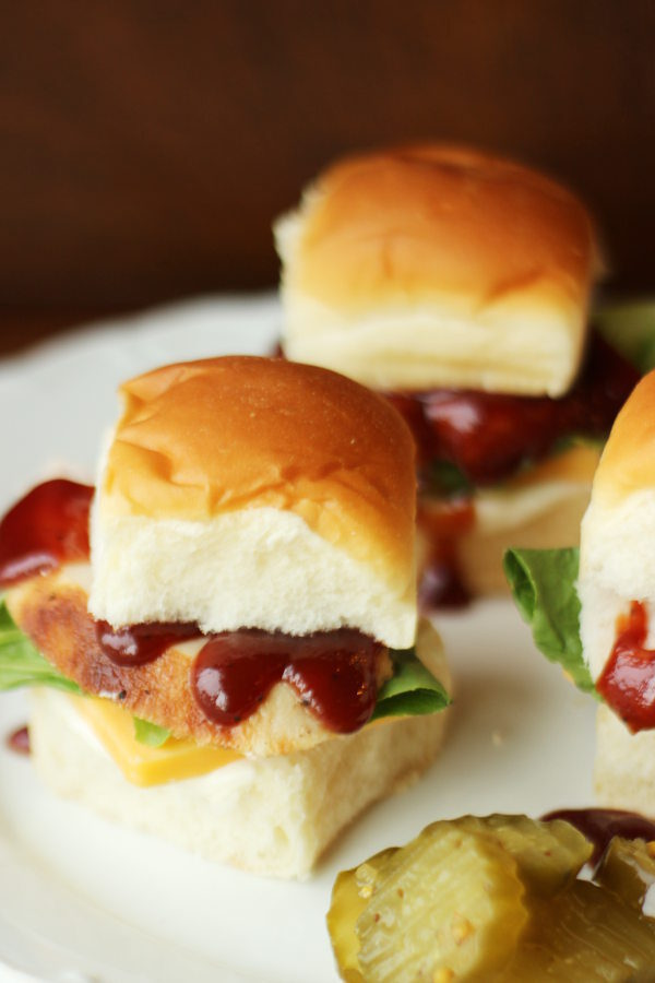 Three little bbq turkey sandwiches sit on a white plate with a pile of sweet pickles. The sandwiches are made with Hawaiian rolls, bbq sauce, slices of leftover turkey, cheese and lettuce.