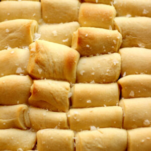 A big pan of buttery Parker House Rolls waits to be eaten on Thanksgiving. You can see a sprinkle of salt crystals on top.