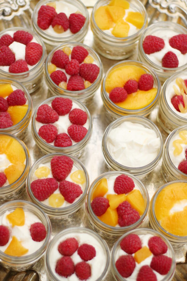 A tray is full of easy no bake fruit tarts covered in raspberries and peaches. The tarts are in tiny mason jars.