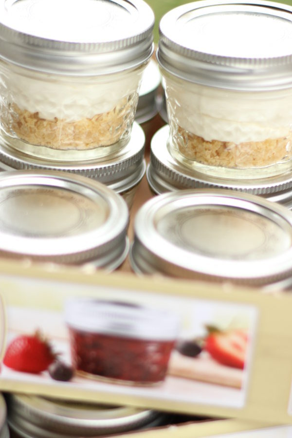 Small fruit tarts are made in 4oz mason jars. You can see the layer of shortbread cookie crust, creamy filling, and then the lids on top so they can be stacked for stoarage.