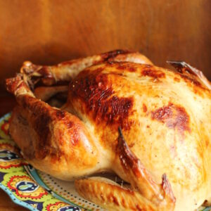 A beautiful brined and roasted turkey sits on a Spanish platter ready to be enjoyed. The platter is on a wooden table.