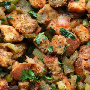 An up close image of turkey stuffing. You see big chunks of golden bread, onions, celery, and plenty of bright herbs.