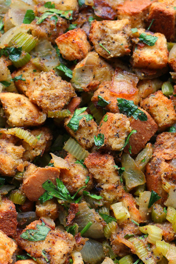 An up close image of homemade turkey stuffing baked in a casserole pan. You see big chunks of golden bread, onions, celery, and plenty of bright herbs.