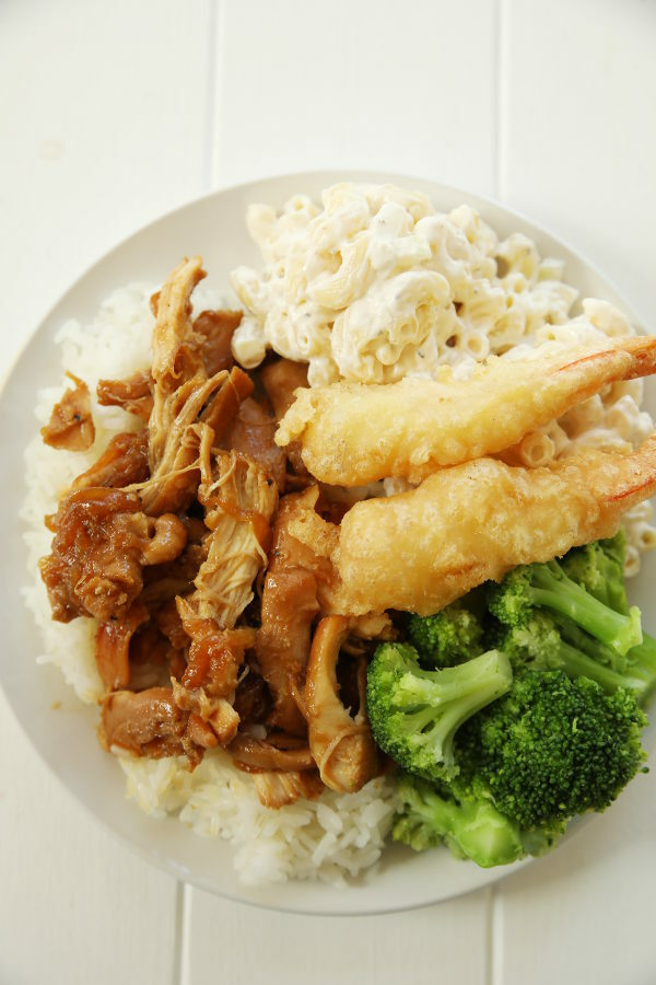 A big white plate is loaded up with rice covered in huli huli chicken. There is a big scoop of Mac Salad and a heap of broccoli with two tempura shrimp on top.