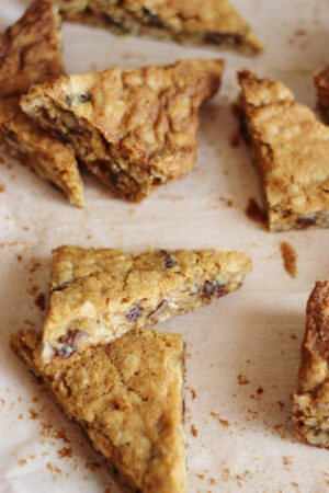 Oatmeal raisin cookie bars are cut into triangles and scattered on parchment paper.