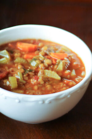 A large white bowl of Spanish lentil soup. You can see celery, carrots and lentils in a savory red broth.