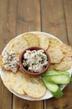 A platter of crackers and cucumbers has a dish of deviled ham spread in the middle waiting to be enjoyed.