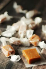 A dark wood table is covered with wrapped caramels. One caramel square is unwrapped ready to taste!