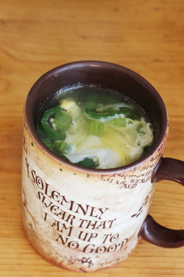 Large mug on a table full of soup. You can see a slice of jalapeno, the cooked egg, and a nice broth in the soup.