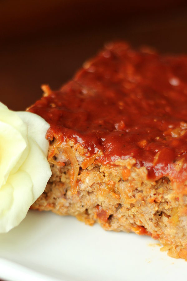 A tender loaf of meatloaf is sliced on a white plate. You can see the edge of a white rose next to the meatloaf.