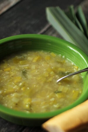 A green bowl of leek soup sits on a table. The soup is full of chicken broth and sautéed leeks.