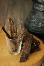 Beef jerky made with ground meat sits in a clear glass cup on a cutting board. More strips of jerky are laid next to it. Behind the jerky is a black pitcher.