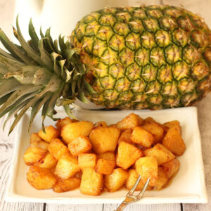 Chunks of pineapple roasted with brown sugar, cinnamon and butter. The pineapple is piled on a white plate in front of a whole pineapple.