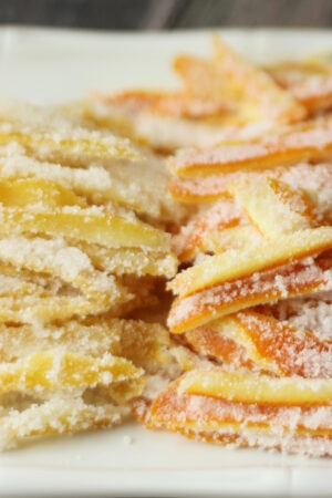 A white platter is stacked high with bright yellow strips of candied lemon peel and bright orange strips of candied orange peel. Both stacks of candied citrus peel glisten with sugar.