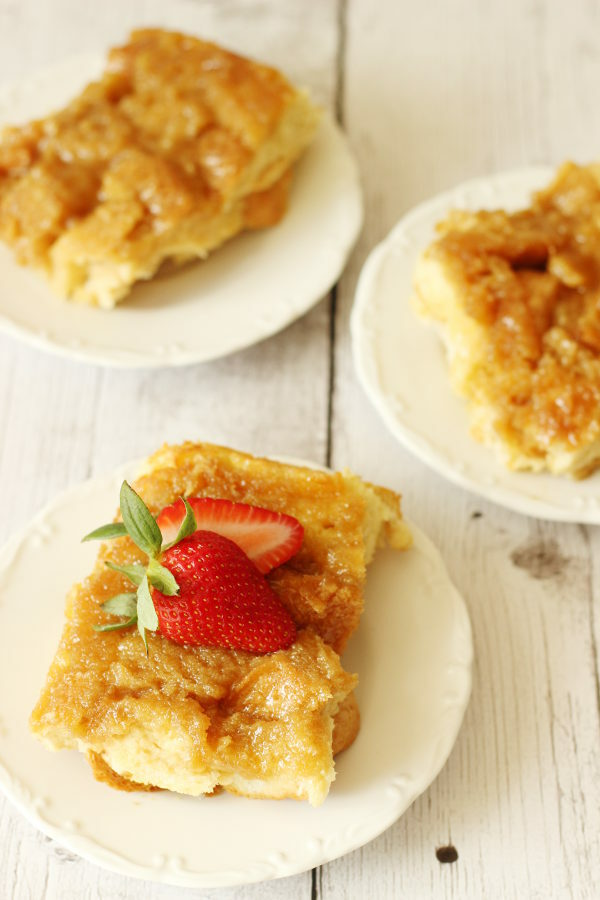 Three slices of creme brulee french toast casserole on white plates. One slice has strawberries on top.