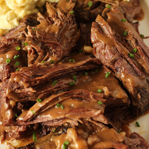 This slow cooker pot roast is piled high on a platter, drizzled with brown gravy and served with a fluffy pile of Yukon gold mashed potatoes.