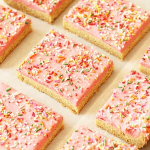 Fresh baked sugar cookie bars are laid out in a grid on parchment paper. The bars are frosted with pink raspberry buttercream and covered with brite sprinkles.