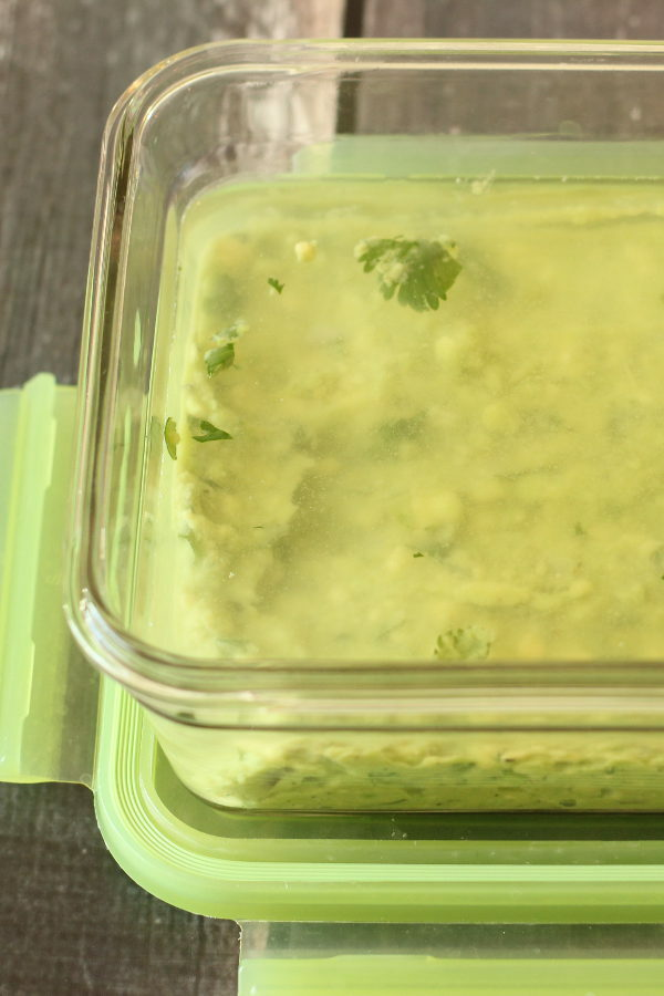 A glass container is full of guacamole. There is a layer of water on top to keep it from browning.