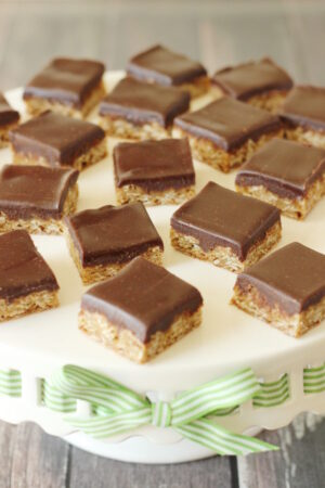 Oatmeal cookie bars are arranged on a white cake stand. Each bar is covered with a thick layer of rich chocolate frosting.