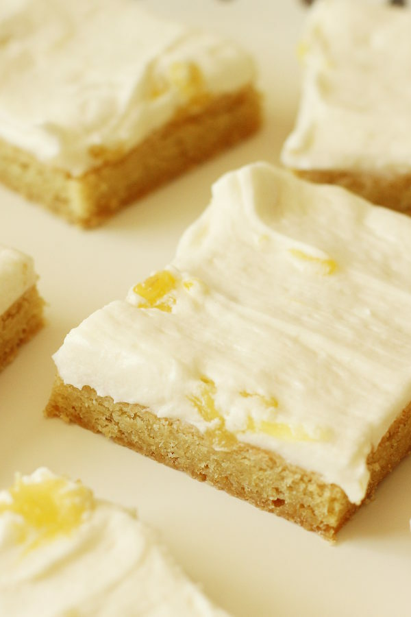 A tray is lined with parchment paper and squares of sugar cookie bars sit on the paper. You can see the coconut-pineapple buttercream frosting on top of the bars. There are chunks of pineapple visible too.