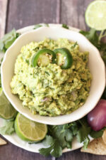 A white bowl is mounded high with chunky, fresh, guacamole. It is garnished with a few jalapenos and surrounded with limes, cilantro and some shallots.